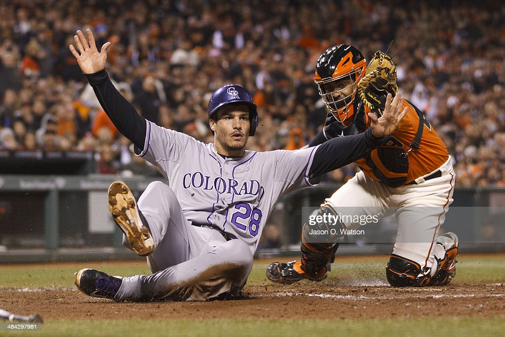 Nolan Arenado #28 of the Colorado Rockies slides past a tag from Hector Sanchez #29 of the San Francisco Giants to score a run during the eighth inning at AT&T Park on April 11, 2014 in San Francisco, California.