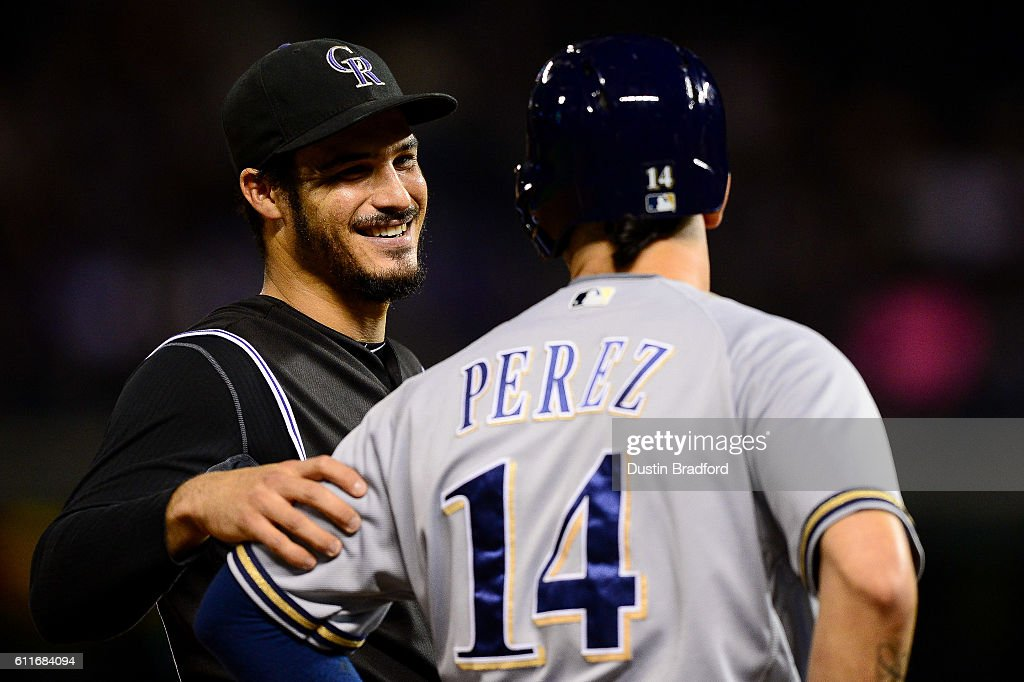 Nolan Arenado #28 of the Colorado Rockies smiles and has a word with Hernan Perez #14 of the Milwaukee Brewers during a umpire review in the fourth inning of a game at Coors Field on September 30, 2016 in Denver, Colorado.