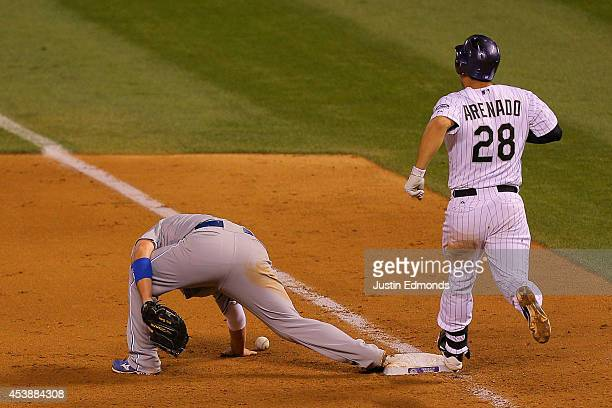 Nolan Arenado of the Colorado Rockies strides into first base safely as first baseman Billy Butler of the Kansas City Royals is unable to make the...