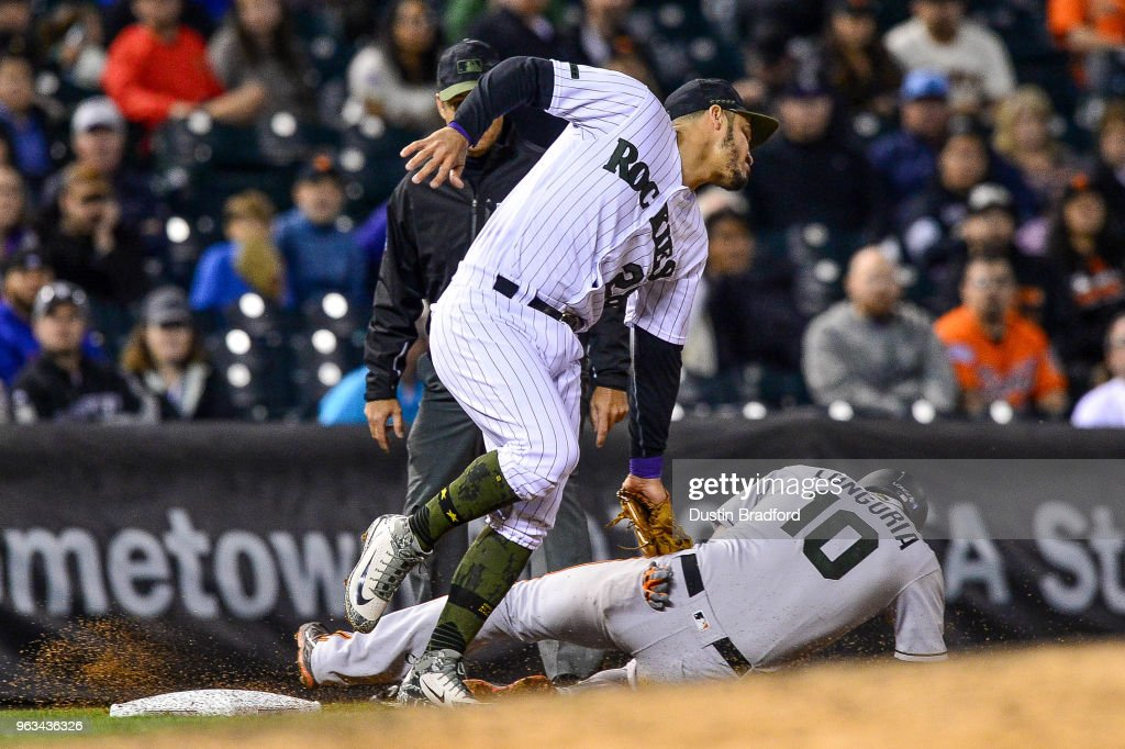 Nolan Arenado #28 of the Colorado Rockies tags out Evan Longoria #10 of the San Francisco Giants at third base for an out in the top of the 10th inning at Coors Field on May 28, 2018 in Denver, Colorado.