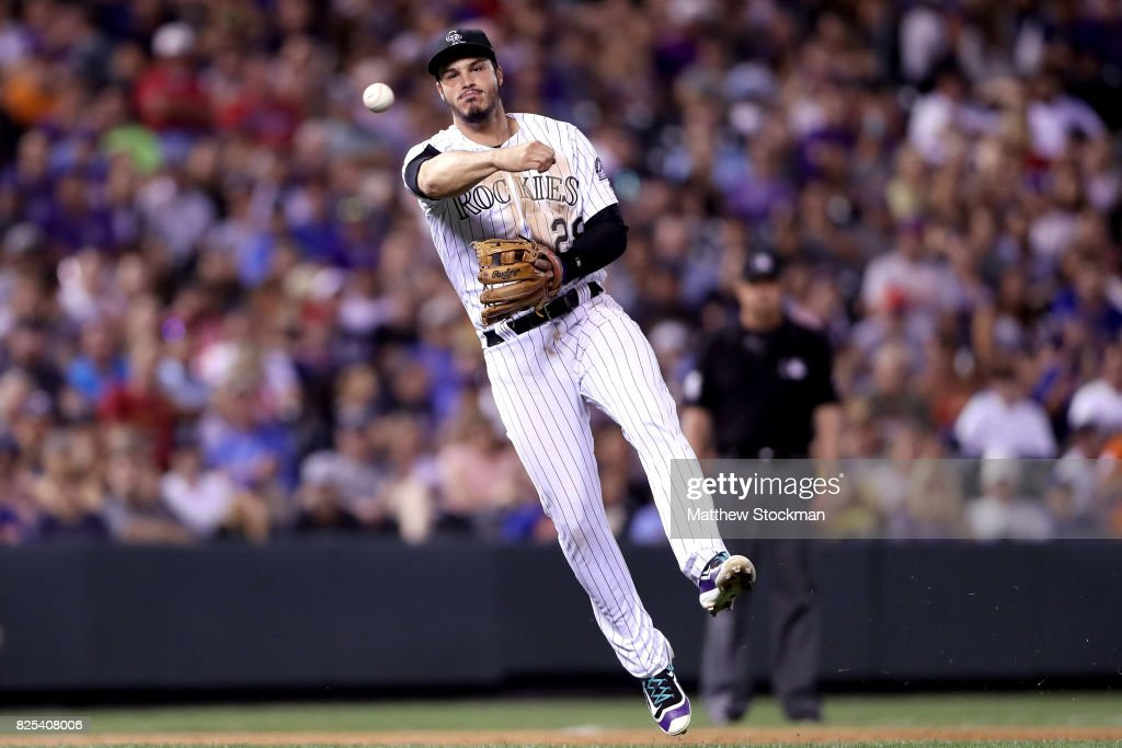 Nolan Arenado #28 of the Colorado Rockies throws out Wilmer Flores of the New York Mets in the eighth inning at Coors Field on August 1, 2017 in Denver, Colorado.