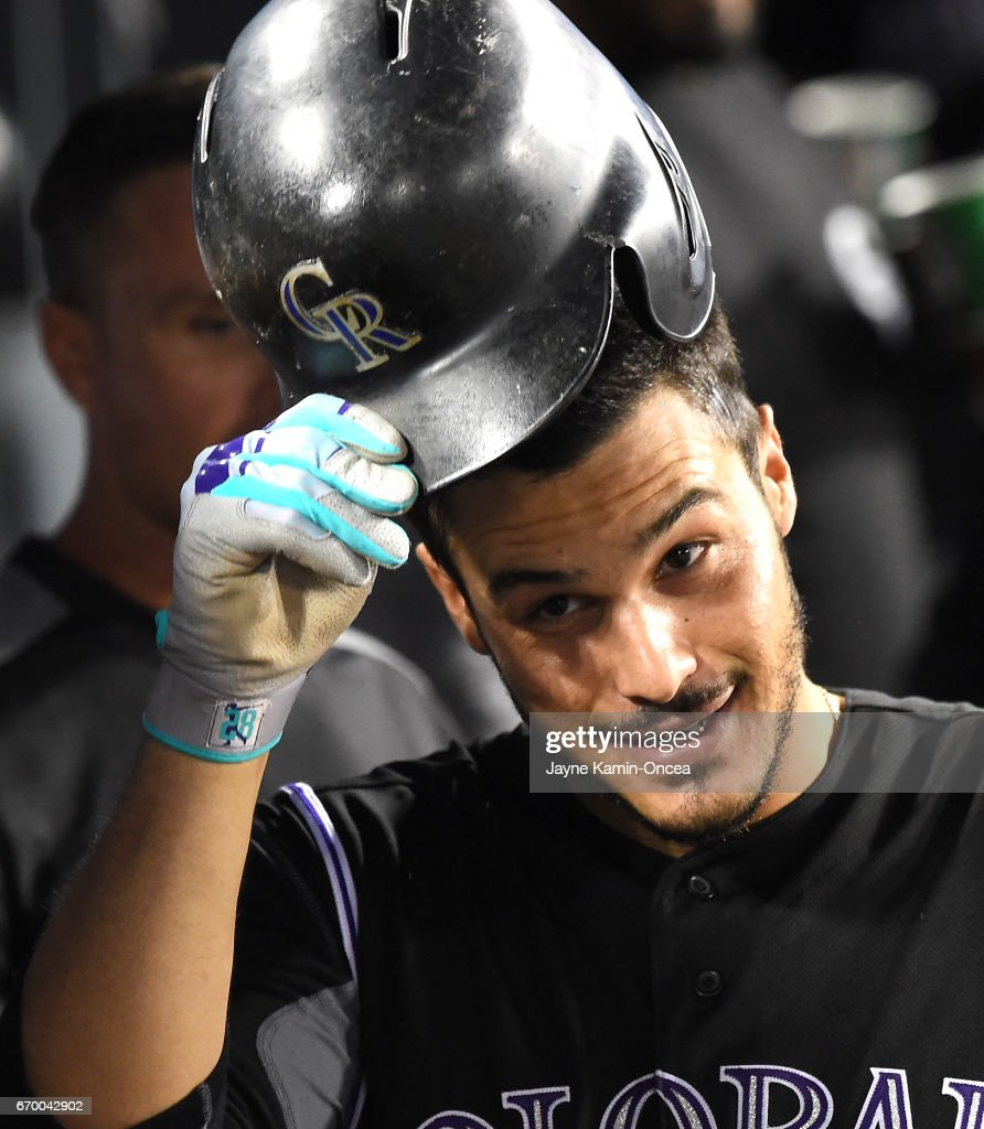 Nolan Arenado #28 of the Colorado Rockies tips his helmet as he is greeted in the dugout after his second home run of the game in the fifth inning against the Los Angeles Dodgers at Dodger Stadium on April 18, 2017 in Los Angeles, California.