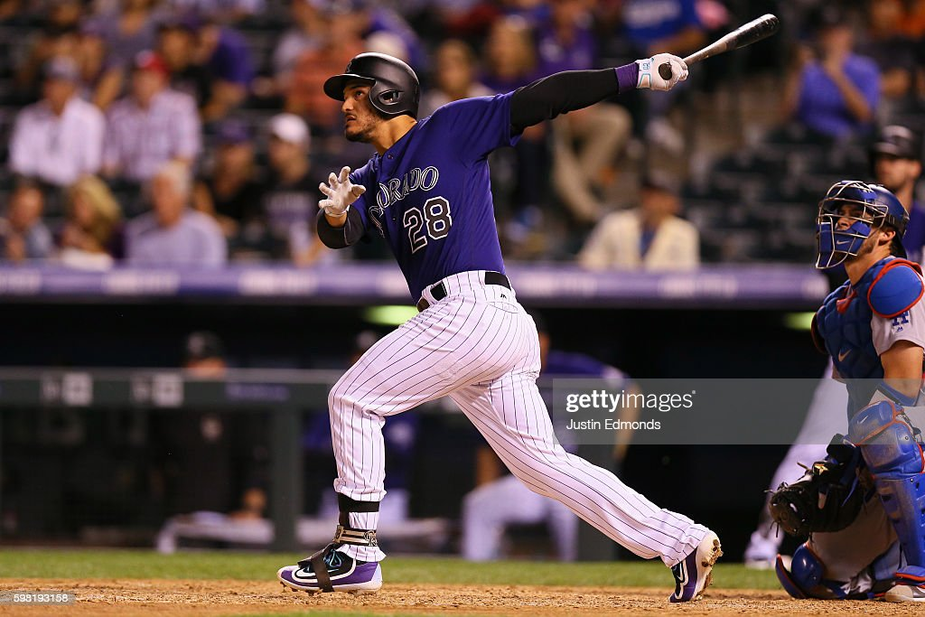 Nolan Arenado #28 of the Colorado Rockies watches his two run home run as catcher Yasmani Grandal #9 of the Los Angeles Dodgers looks on during the seventh inning at Coors Field on August 31, 2016 in Denver, Colorado. The Dodgers defeated the Rockies 10-8 to avoid the series sweep.