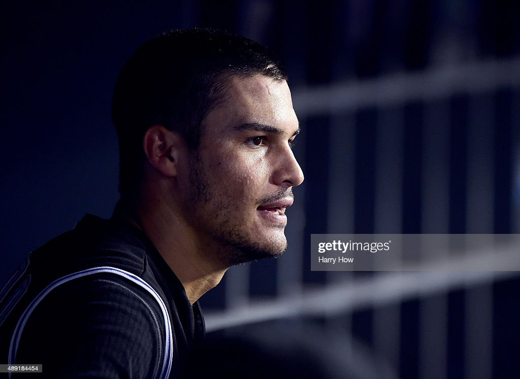 Nolan Arenado #28 of the Colorado Rockies watches play from the dugout after his run to tie the game 1-1 with the Los Angeles Dodgers during the fourth inning at Dodger Stadium on September 15, 2015 in Los Angeles, California.