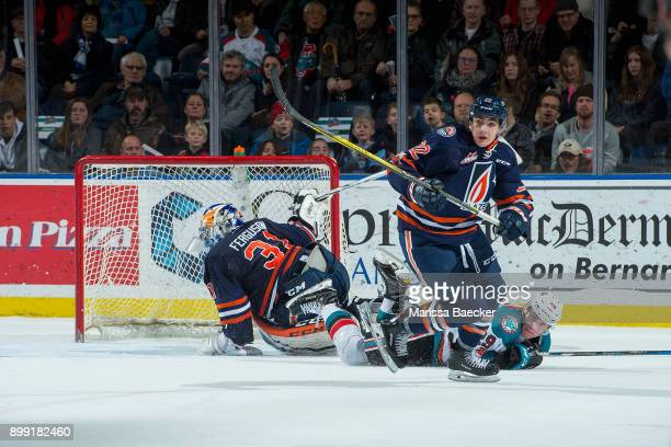 Nolan Foote of the Kelowna Rockets falls to the ice after a check by Quinn Benjafield into the net of Dylan Ferguson of the Kamloops Blazers during...