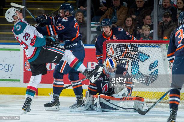 Nolan Foote of the Kelowna Rockets is checked by Nolan Kneen as Dylan Ferguson of the Kamloops Blazers makes a second period save on December 27 2017...