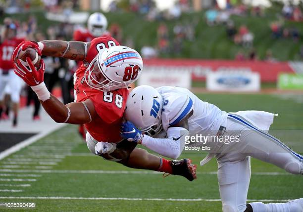 Nolan Givan of the Ball State Cardinals dives across the goal line for a touchdown as he's tackled by cornerback Dexter Lawson of the Central...