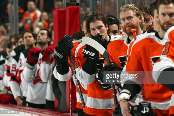 Nolan Patrick and Jakub Voracek of the Philadelphia Flyers stand on the bench with teammates during the National Anthem prior to their game against...