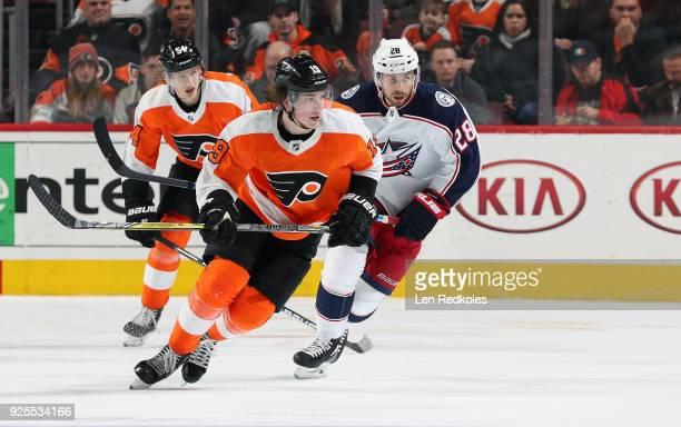 Nolan Patrick and Oskar Lindblom of the Philadelphia Flyers skates against Boone Jenner of the Columbus Blue Jackets on February 22 2018 at the Wells...