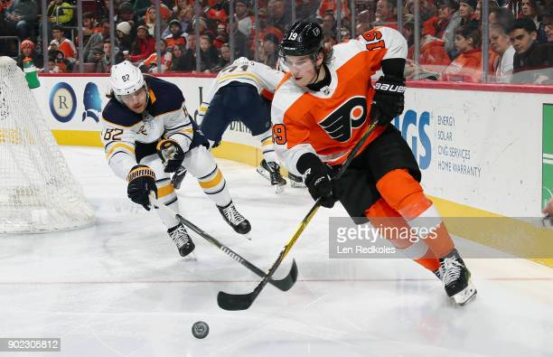 Nolan Patrick of the Philadelphia Flyers battles for control of the loose puck with Nathan Beaulieu of the Buffalo Sabres on January 7 2018 at the...