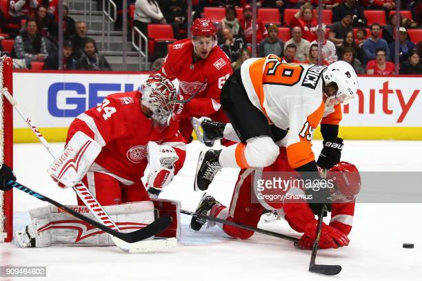 Nolan Patrick of the Philadelphia Flyers battles for the puck between Petr Mrazek and Nick Jensen of the Detroit Red Wings during the third period at...