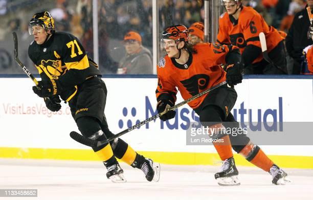 Nolan Patrick of the Philadelphia Flyers skates against Evgeni Malkin of the Pittsburgh Penguins at the 2019 Coors Light NHL Stadium Series on...