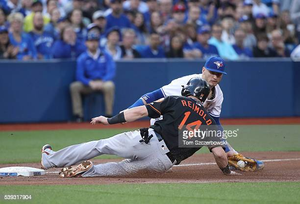 Nolan Reimold of the Baltimore Orioles advances safely to third base in the fifth inning during MLB game action as Josh Donaldson of the Toronto Blue...