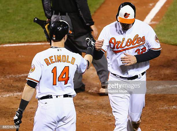 Nolan Reimold of the Baltimore Orioles congratulates Matt Wieters after he scored a run against the Seattle Mariners during the eighth inning on May...
