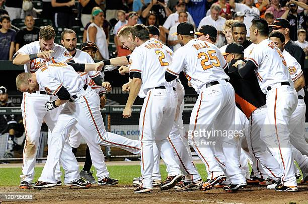 Nolan Reimold of the Baltimore Orioles is mobbed by teammates after hitting the game winning home run in the tenth inning against the Chicago White...