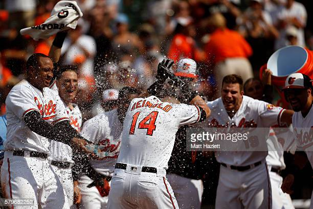 Nolan Reimold of the Baltimore Orioles is swarmed by his teammates at home plate after hitting a two run walkoff home run in the ninth inning to...