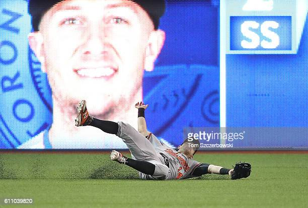 Nolan Reimold of the Baltimore Orioles makes a sliding catch to take a potential hit away from Troy Tulowitzki of the Toronto Blue Jays and turning a...