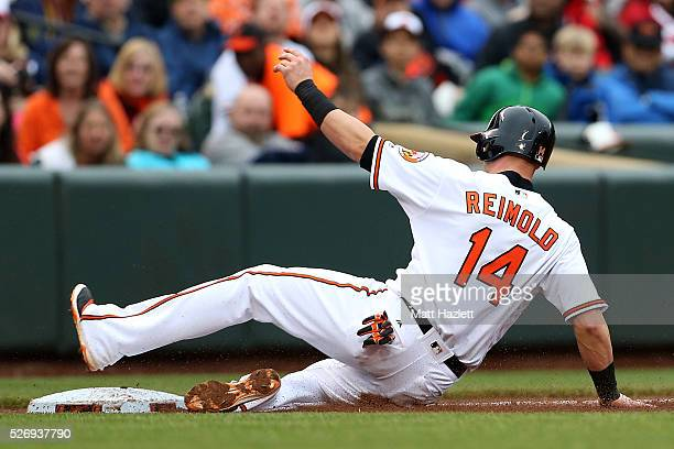 Nolan Reimold of the Baltimore Orioles slides into third base after stealing in the sixth inning against the Chicago White Sox at Oriole Park at...