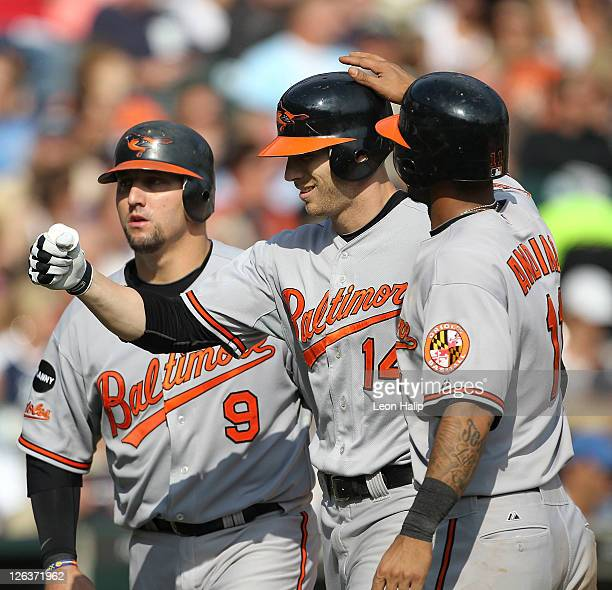 Nolan Reimold of the Baltimore Oriolesis congradualted by Robert Andino and Jake Fox after hitting a three run home run in the eighth inning during...
