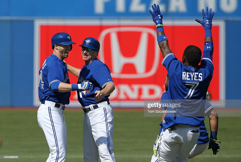 Nolan Reimold #14 of the Toronto Blue Jays is congratulated by first base coach Tim Leiper #34 after hitting the game-winning RBI double in the tenth inning during MLB game action against the Detroit Tigers on August 9, 2014 at Rogers Centre in Toronto, Ontario, Canada.