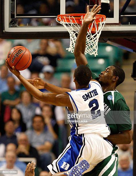 Nolan Smith of the Duke Blue Devils lays in a basket against Kyrie Sutton of the Binghamton Bearcats during the first round of the NCAA Division I...