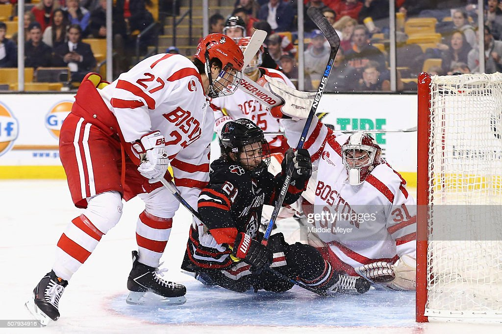 Nolan Stevens #21 of the Northeastern Huskies collides with Sean Maguire #31 of the Boston University Terriers in the goal during the second period at TD Garden on February 1, 2016 in Boston, Massachusetts.