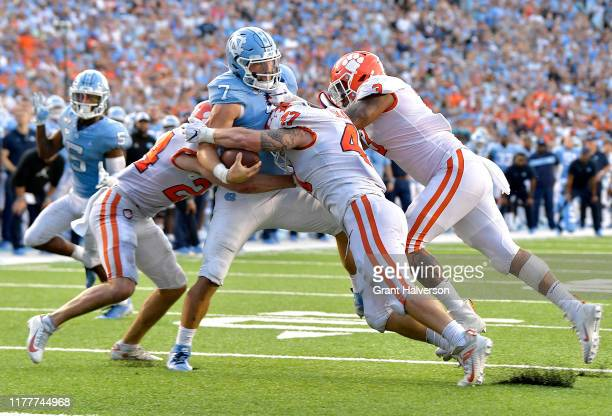 Nolan Turner, James Skalski and Xavier Thomas of the Clemson Tigers stop Sam Howell of the North Carolina Tar Heels short of the goal line on a...