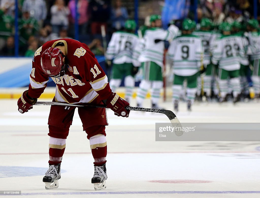 Nolan Zajac #11 of the Denver Pioneers reacts to the loss as the North Dakota Fighting Hawks celebrate the win during semifinals of the 2016 NCAA Division I Men's Hockey Championships at Amalie Arena on April 7, 2016 in Tampa, Florida.
