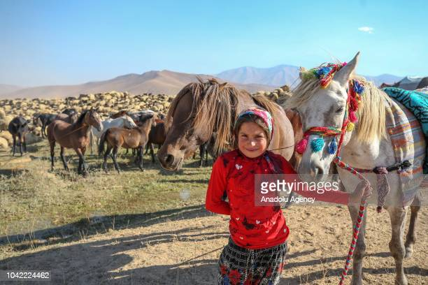 A nomad kid poses for a photo near horses at the fields of Turkey's southeastern province Van on September 26 2018 After cold snap nomads try to...