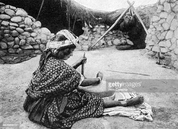 A nomad maid of the mill preparing couscous Algeria 1922 From Peoples of All Nations Their Life Today and the Story of Their Past volume I Abyssinia...