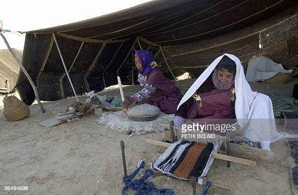 A nomad woman weaves in front of her tent 28 December 2005 during the International Sahara Festival in Douz which reunites various cultural groups...