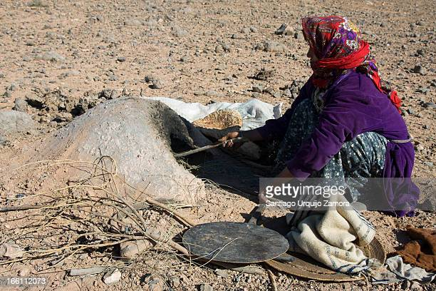 Nomadic Arab woman baking bread in an earth oven in the ground of the rocky desert, in the vicinity of Figuig, Oriental Region, Morocco