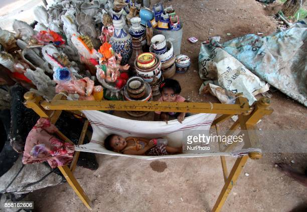A nomadic baby rests at a handmade swing on way side as its parents shelter here to make house hold fancy items and sale it to earn money on the...
