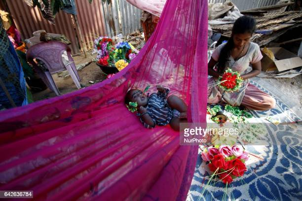 A nomadic baby sleeps in a swing made it in a cloth as it mother prepares fancy flowers for sale to pedestrians on way side in the eastern Indian...