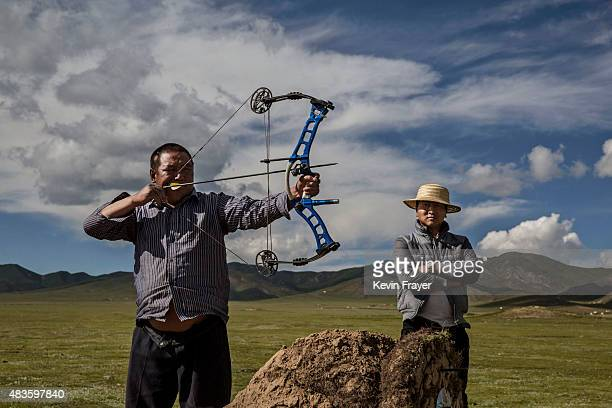 A nomadic ethnic Tibetan man uses a modern bow as he and others take part in a traditional game of archery at their summer camp on July 23 2015 on...