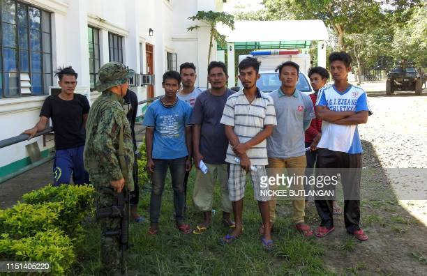 Nomadic fishermen pose for photographs as a Filipino soldier looks at them, after being freed by the Abu Sayyaf group at a military camp in Jolo,...