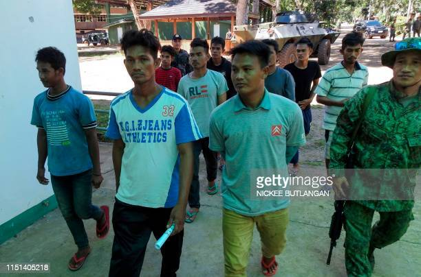 Nomadic fishermen walk along with Filipino soldiers after being freed by the Abu Sayyaf group at a military camp in Jolo Sulu province on the...
