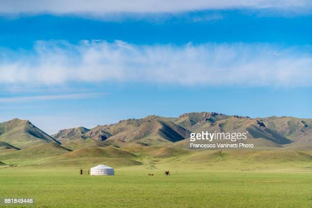 Nomadic ger, motorbike and mountains in the background. Bayandalai district, South Gobi province, Mongolia.