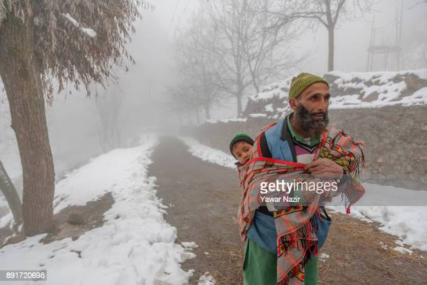 A nomadic Kashmiri man carries a baby in a blanket as he walks on a snow covered road amid dense fog after seasons first snowfall on December 13...