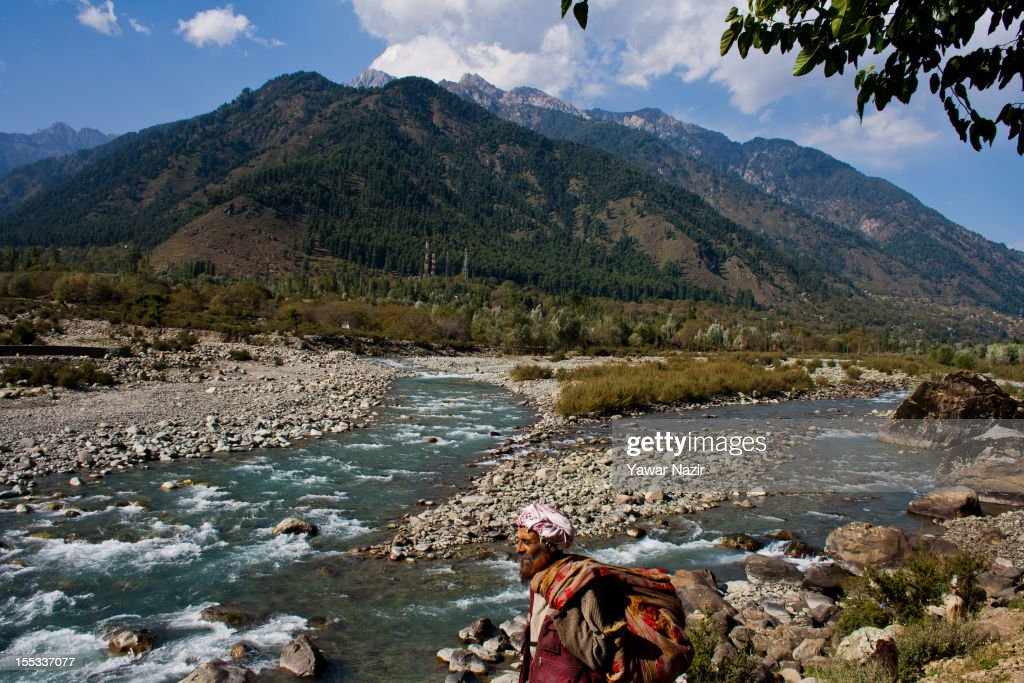 A nomadic Kashmiri man walks on the banks of Lidder stream on November 3, 2012 in Pahalgam, south of Srinagar, the summer capital of Indian administered Kashmir, India. Pahalgam, the Village of Shepherds, is a popular tourist destination where every year large numbers tourists visit from India and abroad. Tourists enjoy long hikes throughout the areas of Lidderwat, Kolohoi Glacier, Sonmarg and various other mountains around Pahalgam.