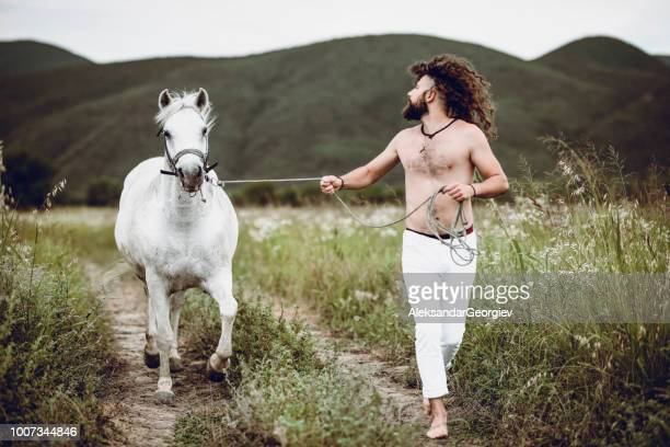 nomadic rancher leading and training horse through meadow - thoroughbred horse stock photos and pictures
