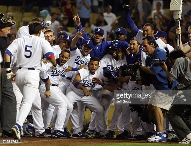 Nomar Garciaparra of the Los Angeles Dodgers is greeted by his teammates at homeplate after hitting a walk off tworun homerun in the tenth inning...