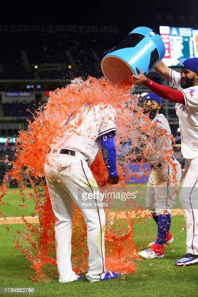 Nomar Mazara of the Texas Rangers and Rougned Odor dump the coolers on Elvis Andrus after the win against the Houston Astros at Globe Life Park in...