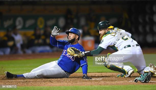 Nomar Mazara of the Texas Rangers gets tagged out at home plate by Jonathan Lucroy of the Oakland Athletics in the top of six inning at the Oakland...