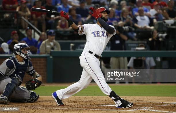 Nomar Mazara of the Texas Rangers hits a solo home run as Jacoby Ellsbury of the New York Yankees looks on during the second inning at Globe Life...