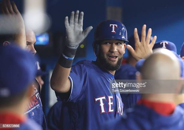 Nomar Mazara of the Texas Rangers is congratulated by teammates in the dugout after scoring a run in the first inning during MLB game action against...