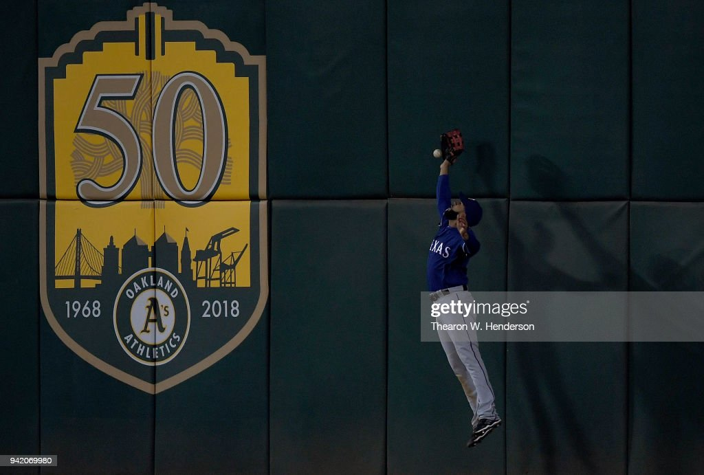 Nomar Mazara #30 of the Texas Rangers leaps at the wall for this ball that goes for a double off the bat of Jed Lowrie #8 of the Oakland Athletics in the bottom of the seventh inning at the Oakland Alameda Coliseum on April 4, 2018 in Oakland, California.