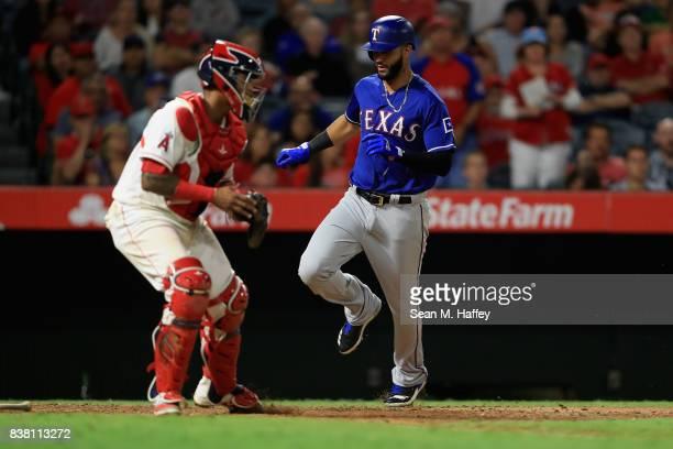 Nomar Mazara scores on a single hit by Robinson Chirinos of the Texas Rangers as Martin Maldonado of the Los Angeles Angels of Anaheim looks on...