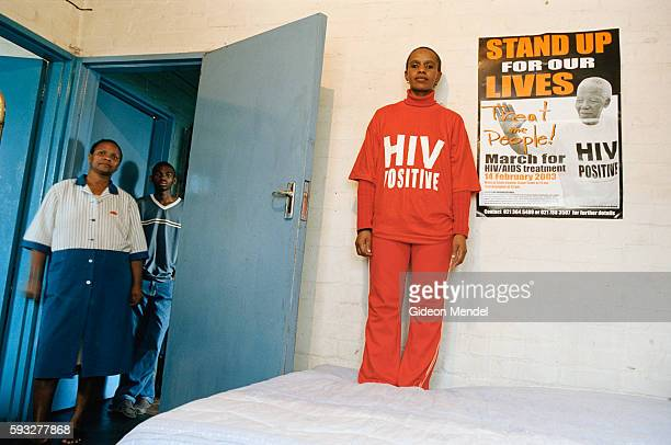 Nombasa Krune stands on her bed next to a TAC poster with a picture of Nelson Mandela advocating AIDS treatment for all She shares the room with her...