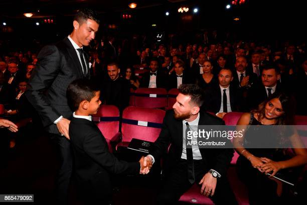 Nominee for the Best FIFA football player Barcelona and Argentina forward Lionel Messi shakes hands with Cristiano Ronaldo Jr son of Real Madrid and...